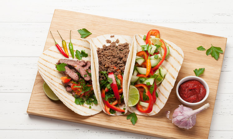 Set of mexican tacos with meat and vegetables in tortilla. Top view on wooden table